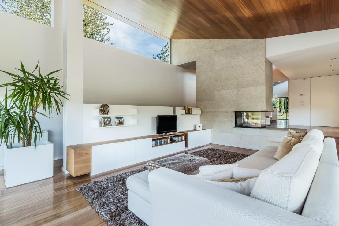 """<p>Remember what we said about allowing the outdoors to come inside? Just see how those clerestory windows bring in buckets of natural lighting that bounce around the sleek and white surfaces.</p><p>And what do you think of wood mixing and mingling with various materials in this<a rel=""""nofollow"""" href=""""https://www.homify.co.uk/rooms/living-room"""">living room</a>, from the concrete fireplace to the expertly upholstered sofa?</p>  Credits: homify / João Boullosa"""