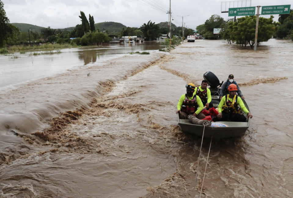 Rescuers navigate a flooded road in a boat after the passing of Hurricane Iota in La Lima, Honduras, Wednesday, Nov. 18, 2020. Iota flooded stretches of Honduras still underwater from Hurricane Eta, after it hit Nicaragua Monday evening as a Category 4 hurricane and weakened as it moved across Central America, dissipating over El Salvador early Wednesday. (AP Photo/Delmer Martinez)