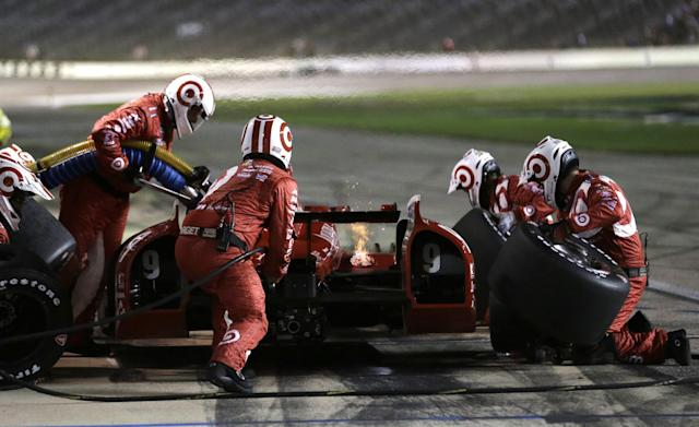 Scott Dixon, of New Zealand, makes a pit stop, as a small fire burns during an IndyCar auto race at Texas Motor Speedway in Fort Worth, Texas, Saturday, June 7, 2014. Dixon returned to racing without incident. (AP Photo/Tim Sharp)