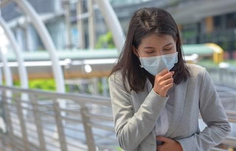 Sick woman wearing a face mask - Credit: Getty