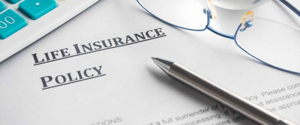 life insurance policy on a piece of paper, with pen, calculator and glasses on top