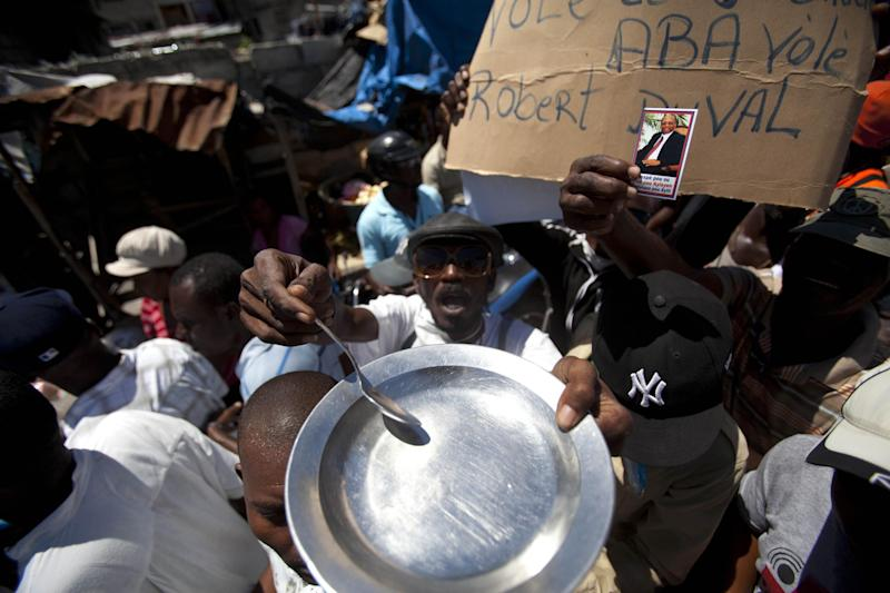 A protester holding an empty plate and a spoon chants anti-government slogans during a demonstration marking the 27th anniversary of the signing of Haiti's Constitution, in Port-au-Prince, Haiti, Saturday, March 29, 2014. Those demonstrating called for the resignation of President Michel Martelly. The protesters say Martelly hasn't done enough to alleviate hunger since he was sworn in as president in May 2011. (AP Photo/Dieu Nalio Chery)