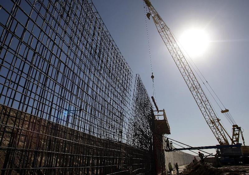 File - In this Feb. 4, 2009 file photo, the sun beats down on construction workers constructing the border wall in Granjeno, Texas. If Congress agrees on a comprehensive immigration reform bill, it will probably include a requirement to erect fencing that would wrap more of the nation's nearly 2,000-mile Southwest border in tall steel columns. But the mandate would essentially double down on a strategy that the Customs and Border Protection agency isn't even sure works. (AP Photo/Eric Gay, File)