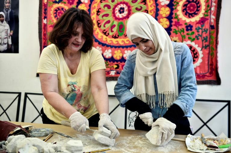 Shaping a future: Brumilda Mustafa Guda, left, an Albanian sculptor, with Syrian refugee Iman al-Bohtori at an art class at the Melissa Center in Athens