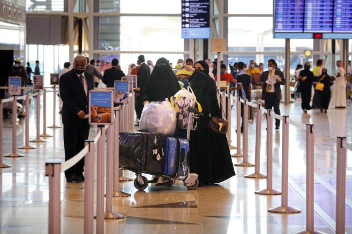 Saudi passengers enter King Abdulaziz International Airport in Jiddah, Saudi Arabia, Monday, May 17, 2021. Vaccinated Saudis will be allowed to leave the kingdom for the first time in more than a year as the country eases a ban on international travel that had been in place to try and contain the spread of the coronavirus and its new variants. (AP Photo/Amr Nabil)