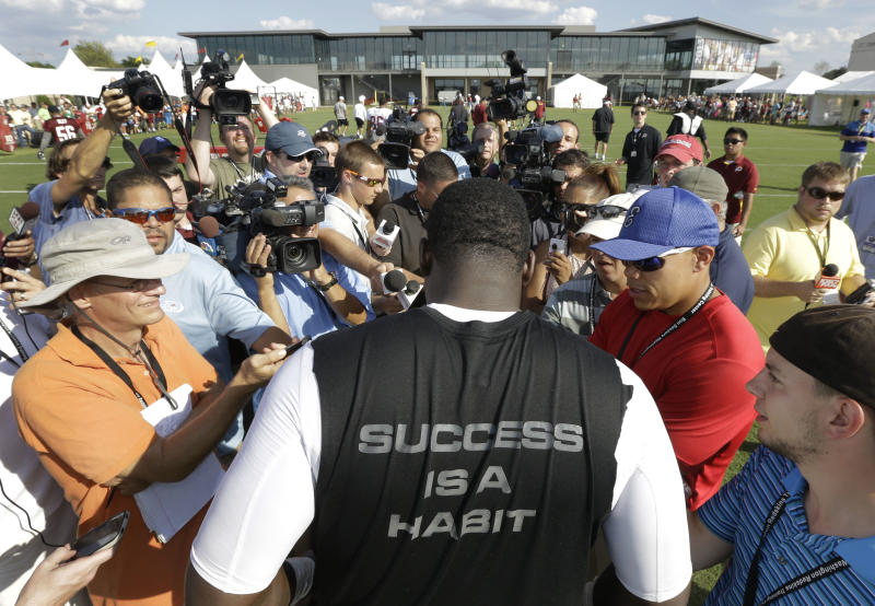 Washington Redskins defensive end Jarvis Jenkins, center, faces reporters after the second day of practice at NFL football training camp in Richmond, Va. Friday, July 26, 2013. Jenkins has been suspended for four games without pay for violating the NFL's policy on performance enhancing substances, the league announced Friday. He remains eligible to practice at training camp and play in preseason games. (AP Photo/Steve Helber)
