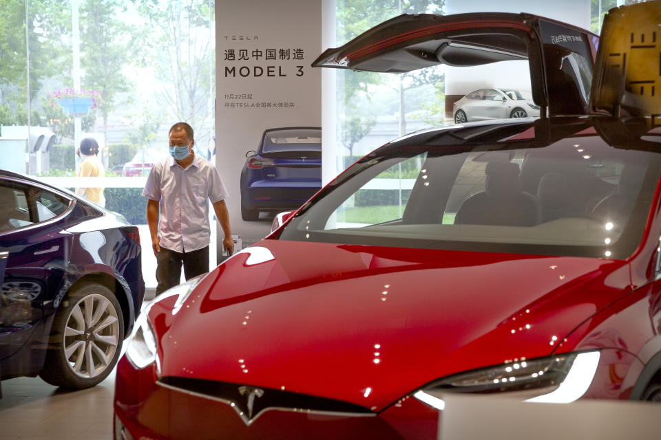 A customer wearing a face mask to protect against the new coronavirus looks at automobiles in a Tesla car showroom in Beijing, Thursday, June 11, 2020. China's auto sales surged 14.5% in May, a second straight month of growth as the global industry's biggest market gradually recovers from the coronavirus pandemic, the China Association of Automobile Manufacturers said Thursday. (AP Photo/Mark Schiefelbein)