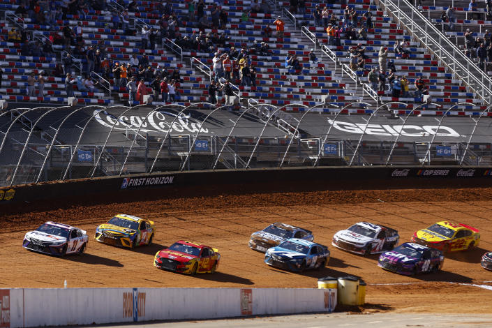 Driver Denny Hamlin (11) leads Kyle Busch (18), Ryan Blaney (12), and others as they enter the back straight to start a NASCAR Cup Series auto race, Monday, March 29, 2021, in Bristol, Tenn. (AP Photo/Wade Payne)