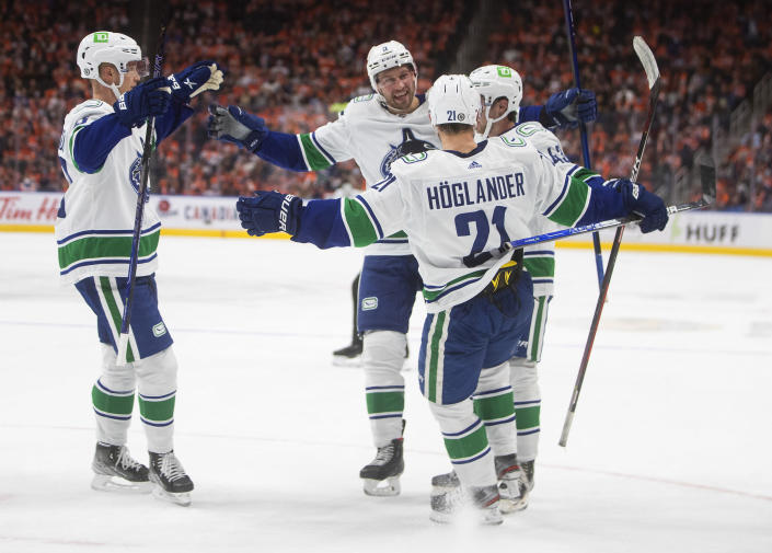 Vancouver Canucks celebrate a goal against the Edmonton Oilers during the third period of an NHL hockey game Wednesday, Oct. 13, 2021, in Edmonton, Alberta. (Jason Franson/The Canadian Press via AP)