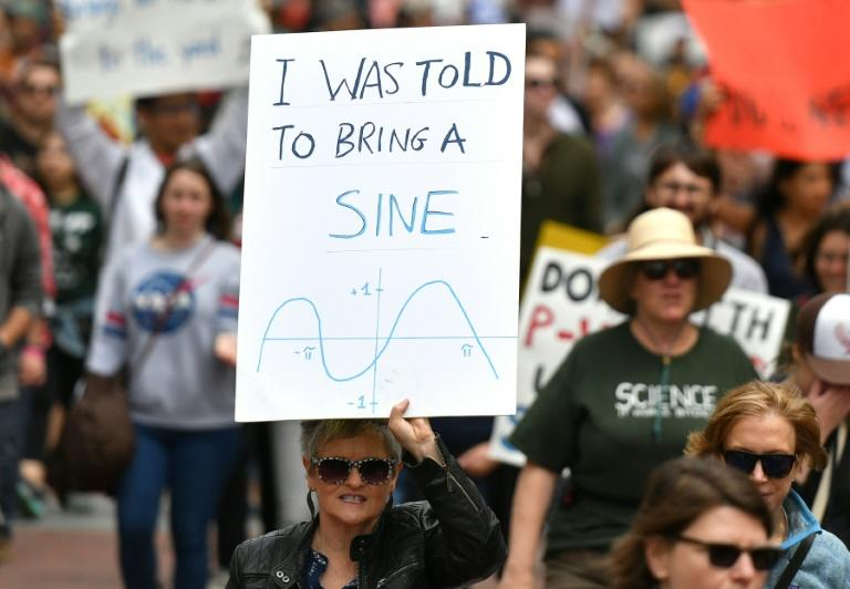 People holds up signs during the March for Science in San Francisco, California on April 22, 2017