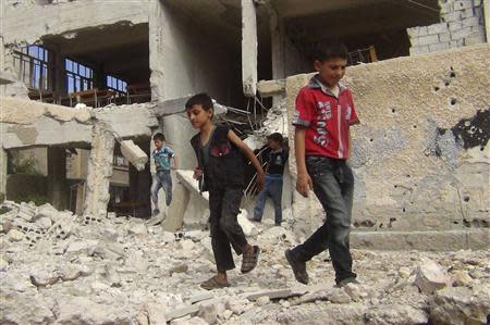 Children walk among debris from a damaged school building in the Damascus suburb of Zamalka