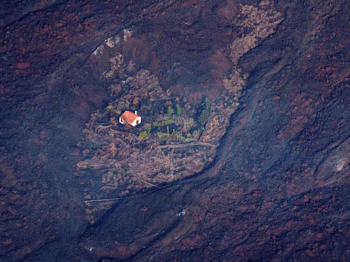 A house in the La Palma, Spain, stands alone in the side of a mountain surrounded by scorch marks.