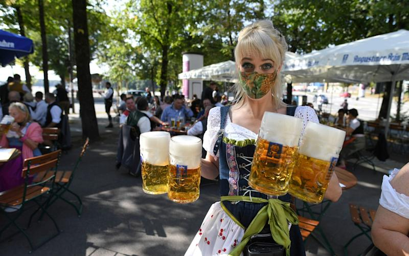 A server carries mugs during a barrel tapping at a beer garden near Theresienwiese where Oktoberfest would have started today - REUTERS