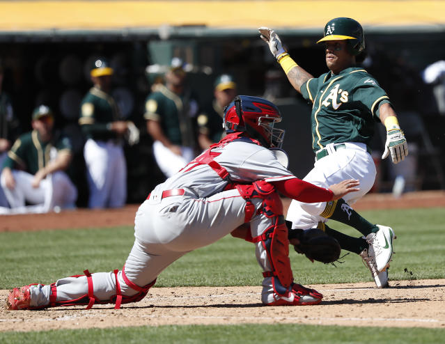 Oakland Athletics' Khris Davis (2) slides past Los Angeles Angels catcher Francisco Arcia (37) to score on a run on a single by Stephen Piscotty during the fourth inning in a baseball game in Oakland, Calif., Thursday, Sept. 20, 2018. (AP Photo/Tony Avelar)