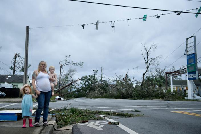 <p>A woman and her children wain near a destroyed gas station after Hurricane Michael in Panama City, Fla., on Oct. 10, 2018. (Photo: Brendan Smialowski/AFP/Getty Images) </p>