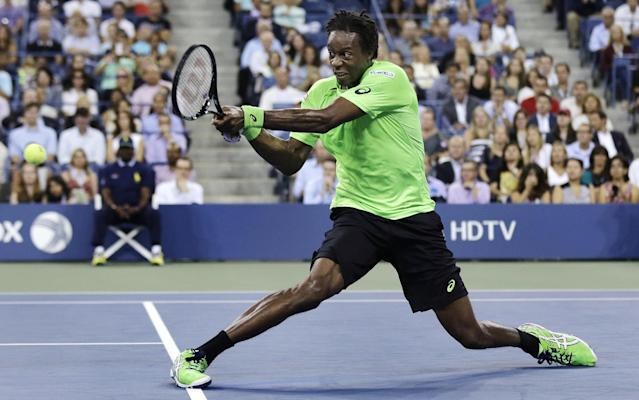Gael Monfils, of France, slides as he returns to Roger Federer, of Switzerland, during the quarterfinals of the U.S. Open tennis tournament, Thursday, Sept. 4, 2014, in New York. (AP Photo/Charles Krupa)