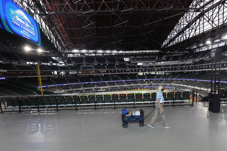 A Texas Rangers employee pulls a cart down an empty concourse at Globe Life Field, home of the Texas Rangers baseball team, in Arlington, Texas, Monday, June 1, 2020. It used to be that empty seats caused palpitations in team owners and college administrators relying on ticket sales and concessions to balance the budget. Now, those empty seats, and short lines and clear concourses, will be the norm for a while as sports grapples with social distancing requirements in the age of coronavirus. (AP Photo/LM Otero)