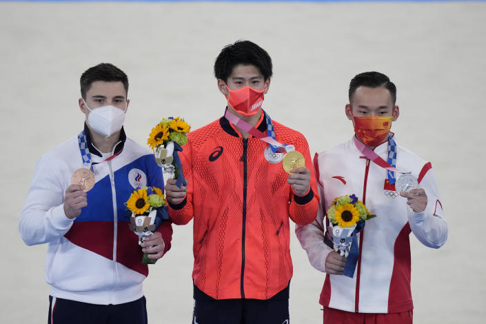 From right to left, silver medallist China's Xiao Ruoteng, Gold medallist Daiki Hashimoto of Japan and bronze medallist Nikita Nagornyy, of the Russian Olympic Committee, pose on the podium after the artistic gymnastics men's all-around final at the 2020 Summer Olympics, Wednesday, July 28, 2021, in Tokyo. (AP Photo/Gregory Bull)