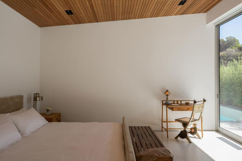 All the rooms in the home benefit from abundant sunlight, as seen in this bedroom. The bed and bedside table were custom designed by Applebaum; the desk is by Jacques Adnet, with a lamp from Marcel Breuer and a chair by Carlo Bugatti sourced from Blackman Cruz. Crisp bed linens by Frette complete the tranquil space.