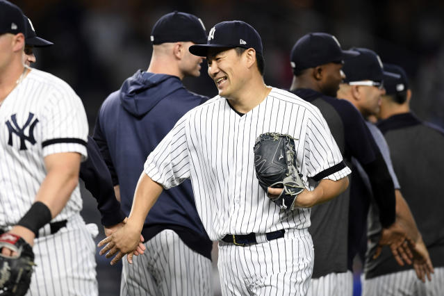 New York Yankees starter Masahiro Tanaka congratulates teammates after pitching a complete baseball game shutout against the Tampa Bay Rays, Monday, June 17, 2019, in New York. (AP Photo/Sarah Stier)