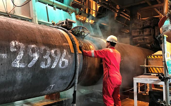 A specialist works onboard the Allseas' deep sea pipe laying ship Solitaire to prepare a pipe for Nord Stream 2 pipeline in the Baltic Sea - REUTERS/Stine Jacobsen/File Photo