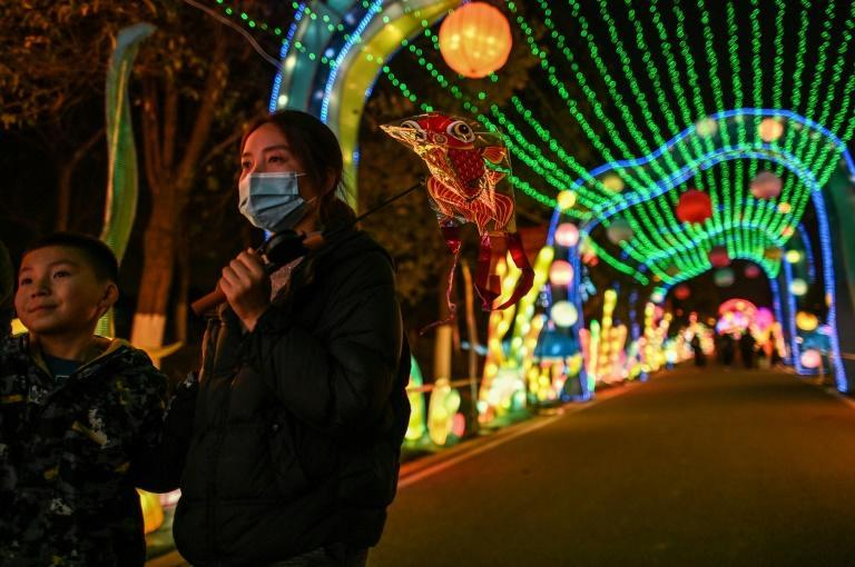 People wear face masks as they walk past lanterns in a park in Wuhan, China ahead of the start of the Lunar New Year, which ushers in the Year of the Ox