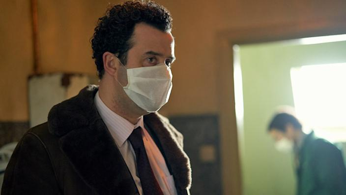 Mays' character wears a mask in one scene because of the smell in Nilsen's flat