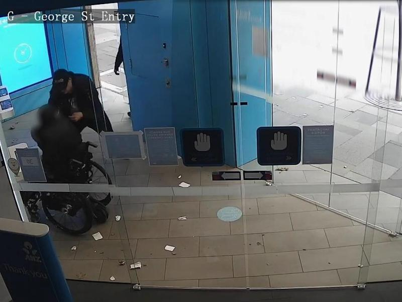 Two men allegedly snatched money out of the hands of a wheelchair user in Sydney: New South Wales Police
