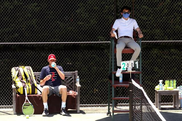 """Sam Querrey, left, takes a drink of water while umpire Albert Ton, masked for protection against COVID-19, waits for action to resume against Brandon Holt during the final round of the Homecourt Advantage tournament on Sunday. <span class=""""copyright"""">(Genaro Molina / Los Angeles Times)</span>"""