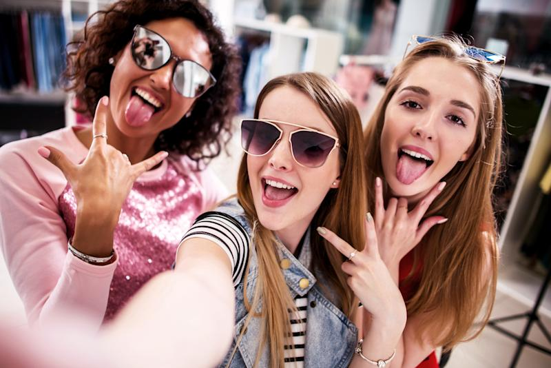 Three young girls taking a selfie while shopping.