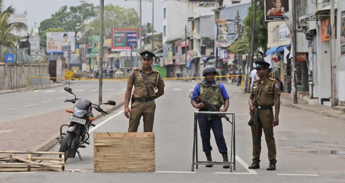 """Sri Lankan policemen and a Naval soldier stand guard at a Check point in Colombo, Sri Lanka, Monday, April 29, 2019. The Catholic Church in Sri Lanka says the government should crack down on Islamic extremists with more vigor """"as if on war footing"""" in the aftermath of the Easter bombings. (AP Photo/Eranga Jayawardena)"""