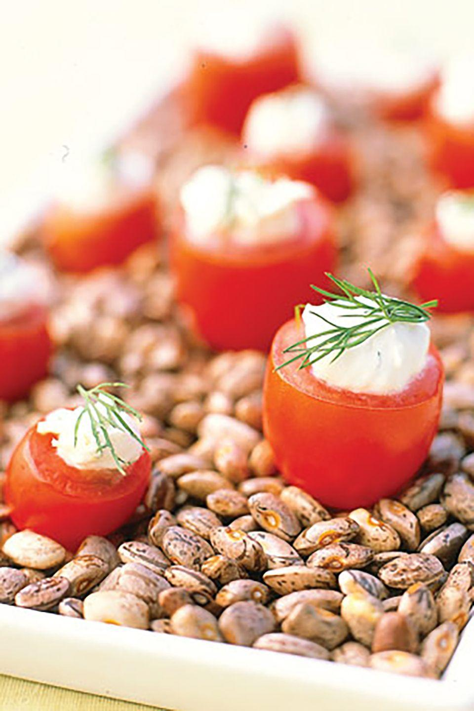 "<p>Stand miniature tomatoes filled with Creamy Lemon-Dill Dip in a tray or shallow serving dish. Shelled, dried runner beans are used here to create an attractive, easy-to-assemble presentation that helps anchor this hors d'oeuvre. Store-bought hummus, baba ghanoush, and tabbouleh can also be enjoyed as a filling. </p><p><strong><a href=""https://www.countryliving.com/food-drinks/recipes/a937/creamy-lemon-dill-dip-3040/?magazine=countryliving"" rel=""nofollow noopener"" target=""_blank"" data-ylk=""slk:Get the recipe"" class=""link rapid-noclick-resp"">Get the recipe</a>.</strong></p><p><a class=""link rapid-noclick-resp"" href=""https://www.amazon.com/Premium-Stainless-Steel-Mixing-Brushed/dp/B01HTYH8YA/?tag=syn-yahoo-20&ascsubtag=%5Bartid%7C10063.g.35089489%5Bsrc%7Cyahoo-us"" rel=""nofollow noopener"" target=""_blank"" data-ylk=""slk:SHOP MIXING BOWLS"">SHOP MIXING BOWLS</a></p>"