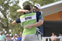 Sam Burns, right, is congratulated by his caddie after putting on the 18th green to win the Valspar Championship golf tournament, Sunday, May 2, 2021, in Palm Harbor, Fla. (AP Photo/Phelan M. Ebenhack)