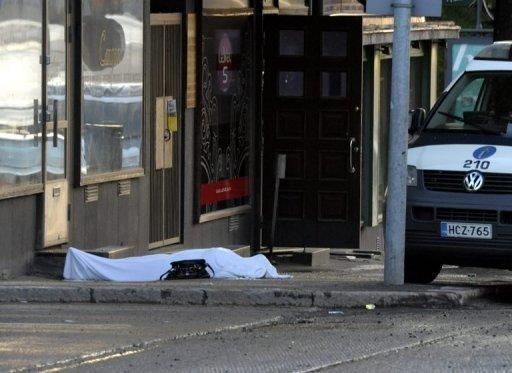 A body lies covered with a sheet following the shooting by a gunman in Hyvinkaa, Finland