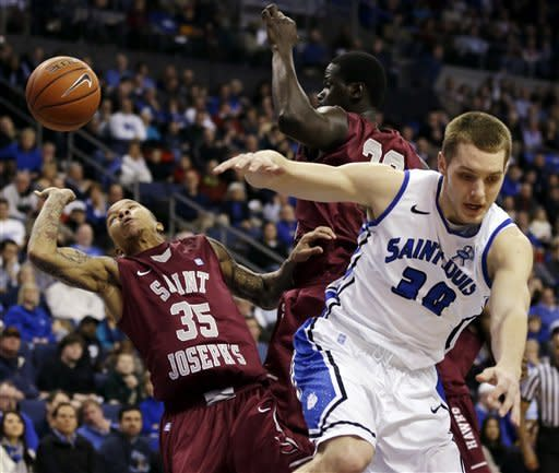 Saint Joseph's guard Carl Jones (35) reaches for a rebound alongside Papa Ndao as Saint Louis forward Jake Barnett, right, falls out of the way during the first half of an NCAA college basketball game, Wednesday, Feb. 27, 2013, in St. Louis. (AP Photo/Jeff Roberson)