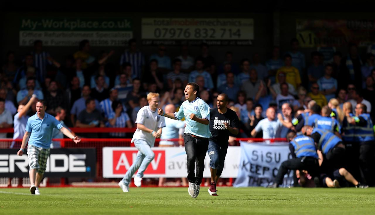 Coventry City fans runs onto the pitch during the Sky Bet League One match at Broadfield Stadium, Crawley.