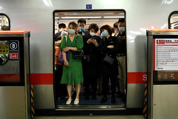 Passengers wearing face masks commute on a subway train during rush hour in Beijing.