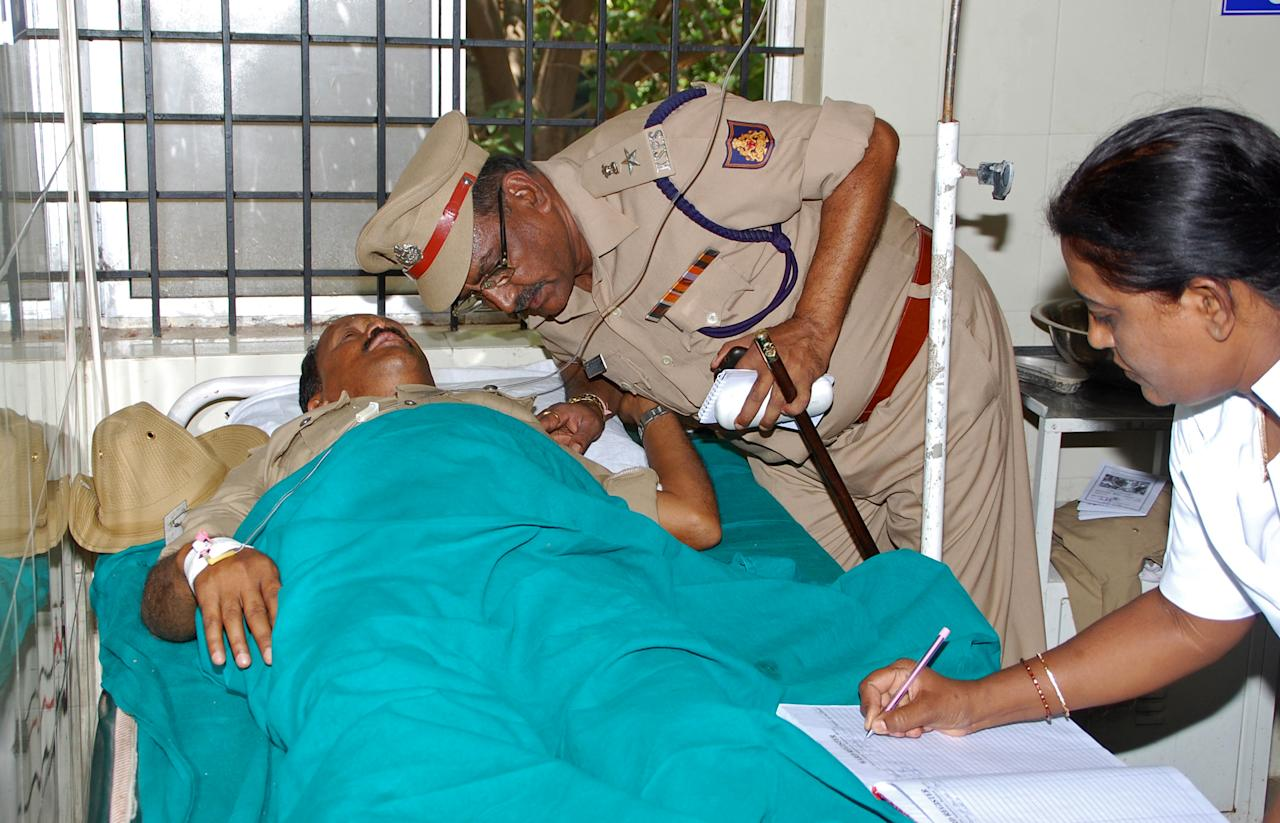 An Indian policeman interacts with a colleague who was injured in a blast near the Bharatiya Janata Party (BJP) office, at a hospital in Bangalore on April 17, 2013. Police in the southern city of Bangalore said Wednesday they were investigating a minor blast outside the office of a political party which injured 12 people.