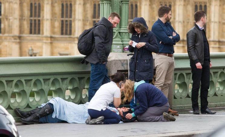 Medics and passers by tending to one of the victims on Westminster Bridge (REX/Shutterstock)