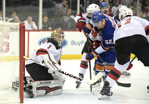 New Jersey Devils goaltender Keith Kinkaid (1) deflects the puck as New York Islanders left wing Ross Johnston (52) skates in during the first period of an NHL hockey game Saturday, Feb. 24, 2018, in Newark, N.J. (AP Photo/Bill Kostroun)