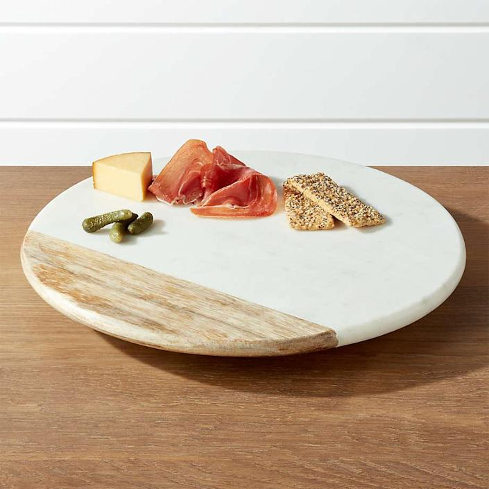 """White marble and mango wood come together to create this sharp-looking cheese board. Not only is it pretty to look at, it rotates 360 degrees for easy access to whatever tops it. (This cheese board is part of an entire wood-and-marble collection including <a href=""""https://www.crateandbarrel.com/wood-and-marble-footed-fruit-bowl/s587386"""" rel=""""nofollow noopener"""" target=""""_blank"""" data-ylk=""""slk:fruit bowls"""" class=""""link rapid-noclick-resp"""">fruit bowls</a>, <a href=""""https://www.crateandbarrel.com/wood-and-marble-salad-servers-set-of-2/s586002"""" rel=""""nofollow noopener"""" target=""""_blank"""" data-ylk=""""slk:serving utensils"""" class=""""link rapid-noclick-resp"""">serving utensils</a>, and more <a href=""""https://www.crateandbarrel.com/wood-marble-inlay-serving-board/s141212"""" rel=""""nofollow noopener"""" target=""""_blank"""" data-ylk=""""slk:serving platters"""" class=""""link rapid-noclick-resp"""">serving platters</a>.) $90, Crate & Barrel. <a href=""""https://www.crateandbarrel.com/wood-and-marble-lazy-susan/s587368"""" rel=""""nofollow noopener"""" target=""""_blank"""" data-ylk=""""slk:Get it now!"""" class=""""link rapid-noclick-resp"""">Get it now!</a>"""