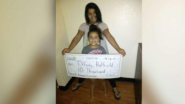 PHOTO: Two of Tiffany Hatfield's three daughters hold her winning lottery check for $10,000. (Tiffany Hatfield )
