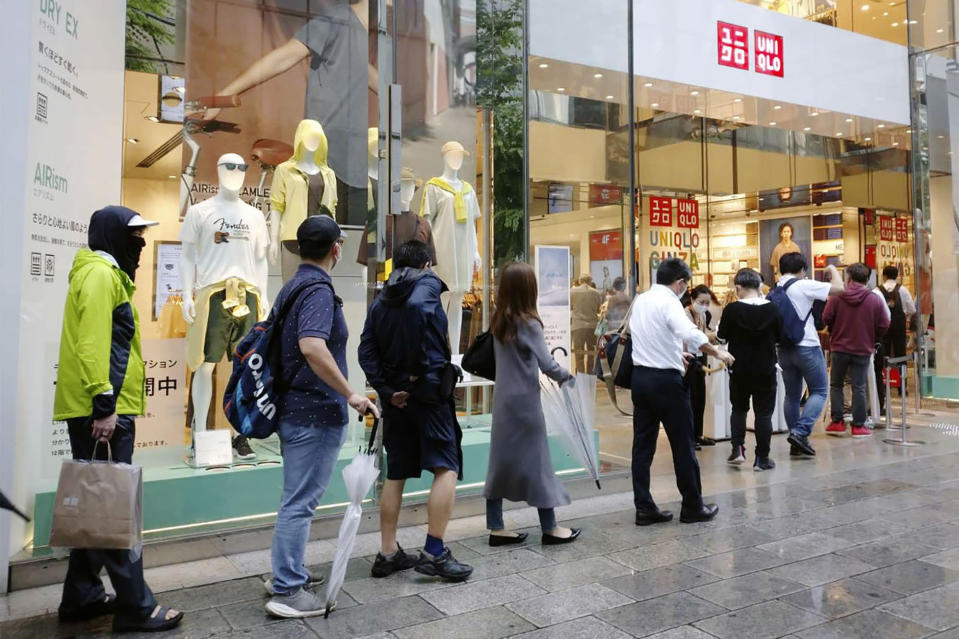 People wait in line at a Uniqlo clothing store at Ginza shopping area in Tokyo, Friday, June 19, 2020. Japanese shoppers queued up in a long line at Uniqlo stores and others clogged up the company's online shopping site Friday as they rushed to buy washable face masks made from the fashion brand's fabric for popular underwear line for summertime use.(Kyodo News via AP)
