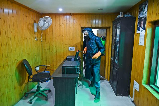 Municipal workers spray disinfectant in a local newspaper's office amid concerns over the spread of the COVID-19 novel coronavirus in Srinagar.