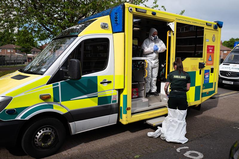 An ambulance crew from the South Central Ambulance Service remove their PPE3-level clothing after responding to a false alarm call for a heart attack in Portsmouth, south England on May 5, 2020. - As the list of recognised Covid-19 symptoms grows, paramedic crews like those with the South Central Ambulance Service are forced to treat every patient as being a potential case, often requiring specialised personal protective equipment (PPE). Paramedics now routinely don what the NHS refers to as Level 2 PPE, like face masks and disposable aprons. (Photo by Leon Neal / POOL / AFP) (Photo by LEON NEAL/POOL/AFP via Getty Images)