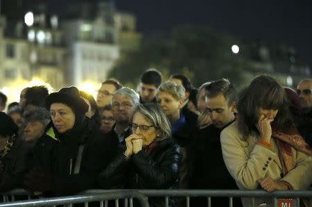 People gather outside Notre Dame Cathedral where a mass is held following a series of deadly attacks in Paris, November 15, 2015. REUTERS/Gonzalo Fuentes
