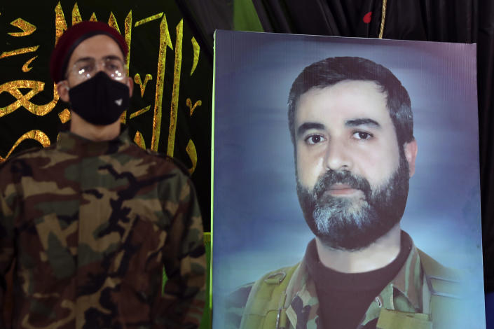 AHezbollah fighter stands next to a picture of Ali Atwa, a senior Hezbollah operative, during his funeral procession in the southern Beirut suburb of Dahiyeh, Lebanon, Saturday, Oct. 9, 2021. Atwa was placed on the FBI's most wanted list in 2001, with two other alleged participants in the 1985 hijacking of TWA Flight 847, one of the worst hijackings in aviation history and that lasted for 16 days. (AP Photo/Bilal Hussein)