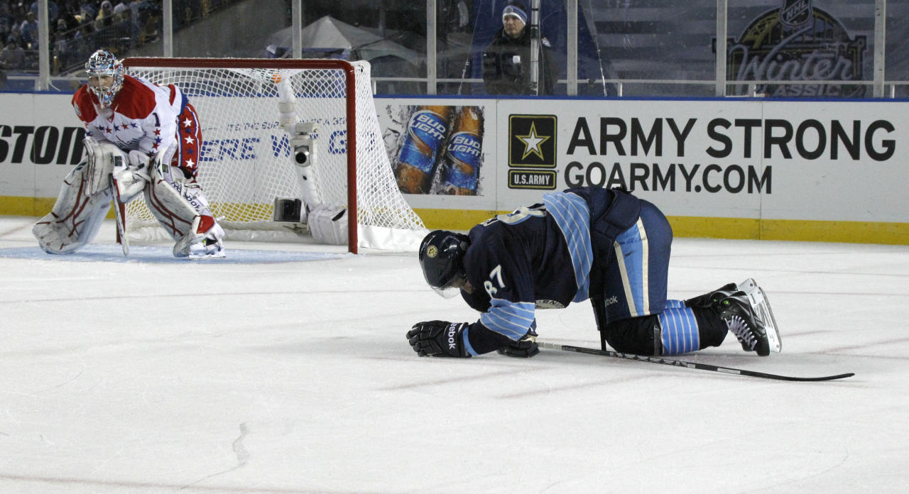 In this Jan. 1, 2011, photo, Pittsburgh Penguins' Sidney Crosby, right, crawls on the ice after being injured in the second period of the NHL Winter Classic outdoor hockey game in Pittsburgh. Washington Capitals goalie Semyon Varlamovis at left. Crosby will make his season debut on Monday, Nov. 21, against the New York Islanders, his first game in nearly a year since being sidelined with concussion-like symptoms. Crosby hasn't played since taking a head shot here and in the next game in January against Tampa Bay. (AP Photo/Keith Srakocic)