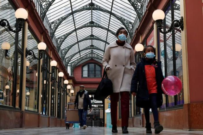 FILE PHOTO: People wearing protective face masks in Paris