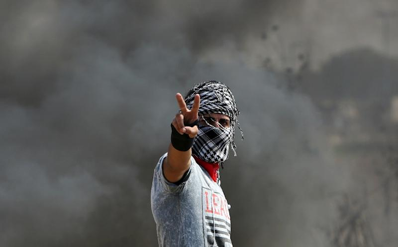 A Palestinian protester flashes the sign for victory during clashes with Israeli security forces near the Nahal Oz border crossing with Israel, east of Gaza City on October 10, 2015